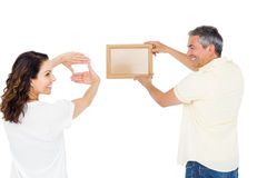 Happy couple holding picture frame Stock Images