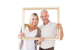 Happy couple holding a picture frame Royalty Free Stock Photos