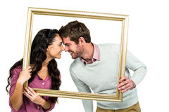 Happy couple holding picture frame Royalty Free Stock Photo
