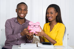 Happy Couple Holding Piggybank Royalty Free Stock Images
