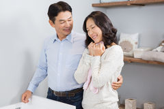 Happy couple holding pink onesie Royalty Free Stock Photos