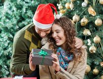 Happy Couple Holding Present Against Christmas Stock Photography
