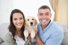 Happy couple holding puppy at home Stock Images