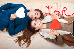 Happy couple holding red heart. Couple kissing behind paper heart Stock Photography