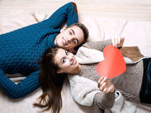 Happy couple holding red heart. Couple kissing behind paper heart, heart focus Stock Photos