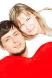 Happy couple holding red heart pillow over white Stock Photos