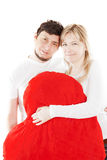Happy couple holding red heart pillow over white Stock Image
