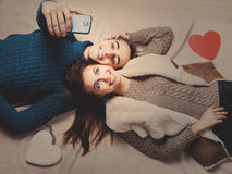 Happy couple holding red heart. Young couple lying on the floor, taking selfie Stock Images