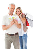 Happy couple holding shopping bags and cash Stock Photos