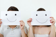 Happy couple holding smileys over their faces Stock Photography