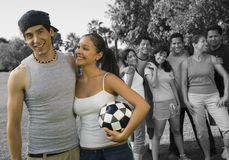 Happy couple holding soccer ball enjoying with friends at park royalty free stock photos