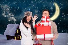 Happy couple holding stack of christmas gifts Royalty Free Stock Image