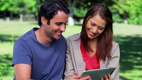 Happy couple holding a tablet computer stock footage
