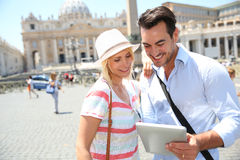 Happy couple holding a tablet in street of Rome Stock Image