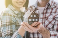 Dream house. Happy couple holding their dream house in their hands, real estate and home insurance concept stock image