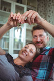 Happy couple holding their house key. At home royalty free stock photos