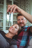Happy couple holding their house key. At home stock photo