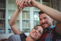 Happy couple holding their house key. At home royalty free stock photo