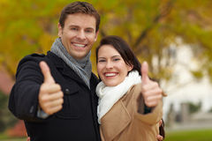 Happy couple holding thumbs up Stock Photos