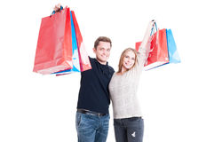 Happy couple holding up bunch of shopping bags Royalty Free Stock Photography