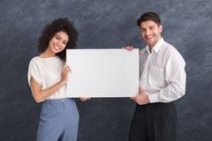 Happy couple holding white banner with copy space royalty free stock photography