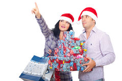 Happy couple holding Xmas gifts and pointing up. Couple holding shopping bags and Christmas gifts pointing  and looking up somehwere isolated on white background Stock Photography