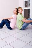 Happy couple at home. A happy couple sitting back to back on the floor at home Royalty Free Stock Photo