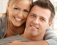 Happy couple at home. Happy couple looking at camera, hugging, smiling Stock Image