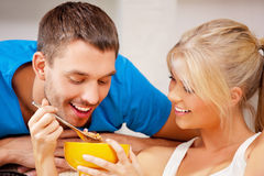 Happy couple at home. Bright picture of happy couple with muesli (focus on man Royalty Free Stock Photos