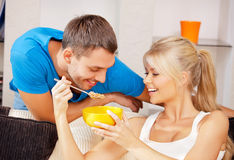 Happy couple at home. Bright picture of happy couple with muesli (focus on man Stock Image