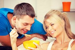 Happy couple at home. Bright picture of happy couple with muesli (focus on woman Royalty Free Stock Photos