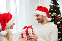 Happy couple at home with christmas gift box Stock Images