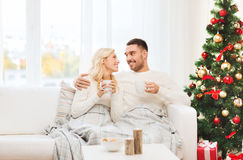 Happy couple at home with christmas tree Stock Image