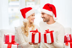 Happy couple at home exchanging christmas gifts Stock Images