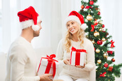 Happy couple at home exchanging christmas gifts Royalty Free Stock Photography