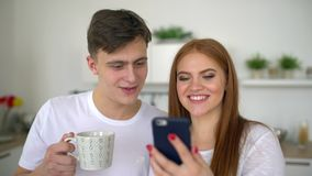 Happy couple at home in kitchen at breakfast using smartphone together browsing online having fun drinking coffee. 4 k. Happy couple at home in kitchen at stock video footage