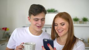 Happy couple at home in kitchen at breakfast using smartphone together browsing online. 4 k. Happy couple use smartphone. Happy couple at home in kitchen at stock video