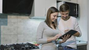 Happy couple at home in kitchen using tablet together stock video footage