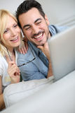 Happy couple at home looking at tablet Stock Photography