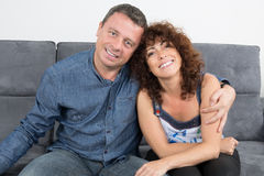 Happy Couple at home relaxing in sofa. At home stock image