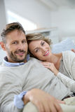 Happy couple at home relaxing on sofa Stock Image