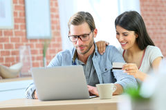 Happy couple at home shopping on laptop Royalty Free Stock Photography