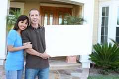 Happy Couple at Home with Sign Royalty Free Stock Images