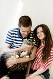 Happy couple at home with their cat Royalty Free Stock Image
