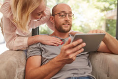 Happy couple at home using digital tablet. Mature men sitting on sofa using digital tablet with his girlfriend standing by with her hands on his shoulders Royalty Free Stock Image
