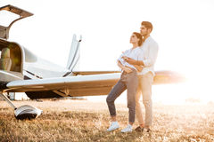Happy couple on a honeymoon standing at the airplane field Stock Image