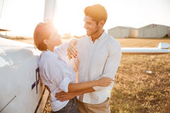 Happy couple on a honeymoon standing at the airplane field Stock Photos