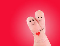 Happy couple hug concept, painted at fingers. Against red background Stock Image