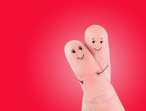 Happy couple hug concept, painted at fingers against red. Background royalty free stock image