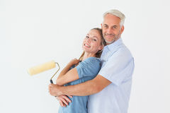 Happy Couple Hugging And Holding Paint Roller Royalty Free Stock Image